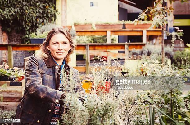 Wunderschöne Gärtner halten eine Pflanze aus Rosmarin