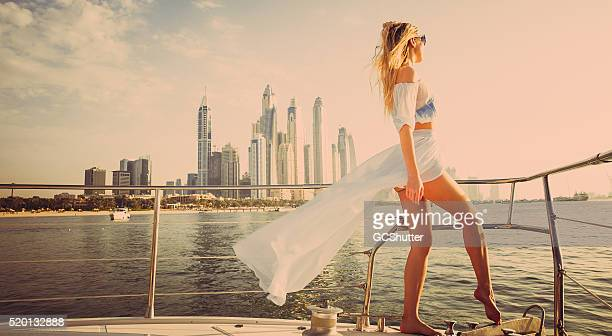 Beautiful girl admiring sunset from a luxury yacht