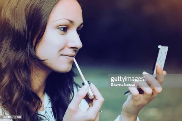 Beautiful girl applying lipstick
