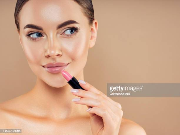 beautiful girl applying make-up - lipstick stock pictures, royalty-free photos & images