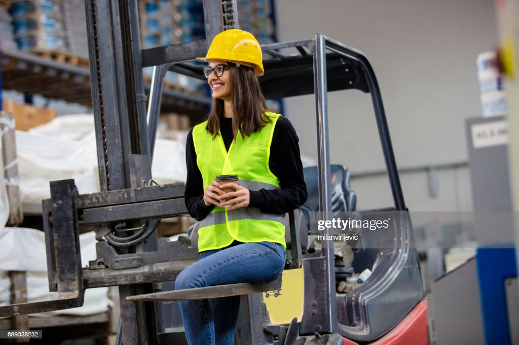 Beautiful girl at factory in a vest and helmet sitting on forklift. : Stock Photo