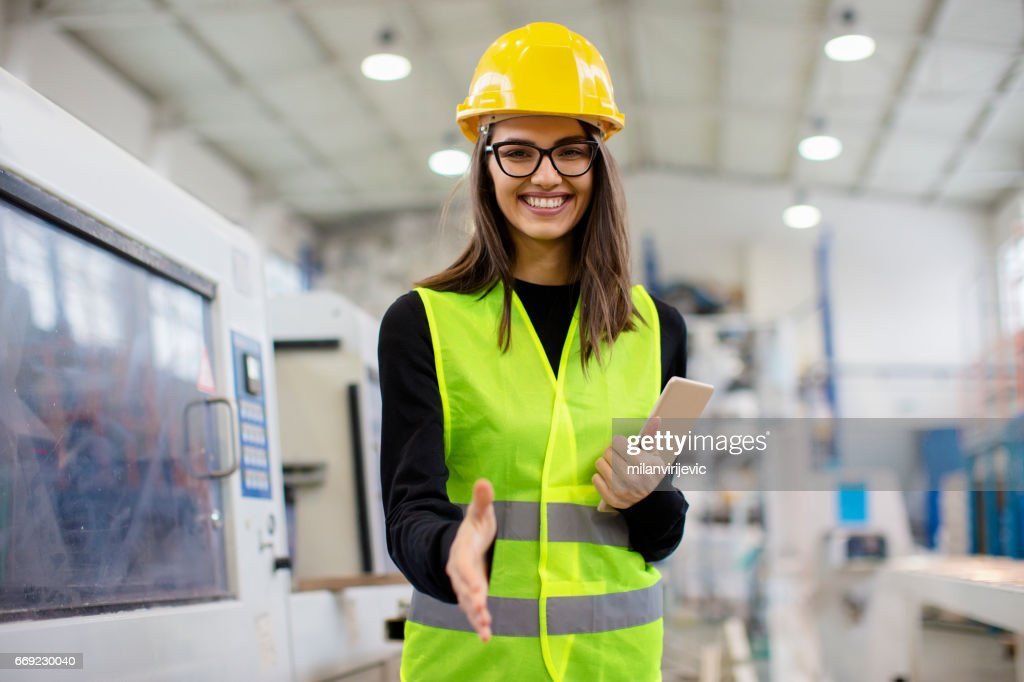 Beautiful girl at factory in a vest and helmet smiling, going for a handshake. : Stock Photo