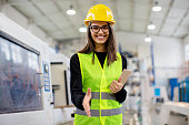 Beautiful girl at factory in a vest and helmet smiling, going for a handshake.