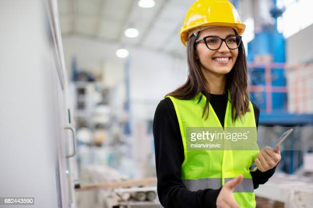 Beautiful girl at factory in a vest and helmet smiling going for a handshake