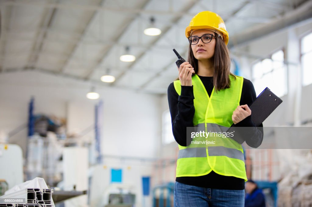 Beautiful girl at factory in a vest and helmet with walkie talkie. : Stock Photo