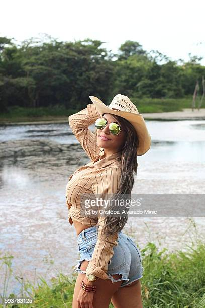 a beautiful girl at the border of a lake - cowgirl hairstyles stock photos and pictures