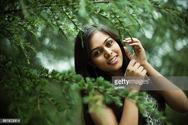 beautiful girl between nature full of branches of pine tree. - girls stock pictures, royalty-free photos & images