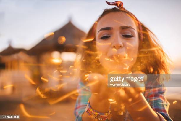 Beautiful  girl blowing glitter in the sun at the beach