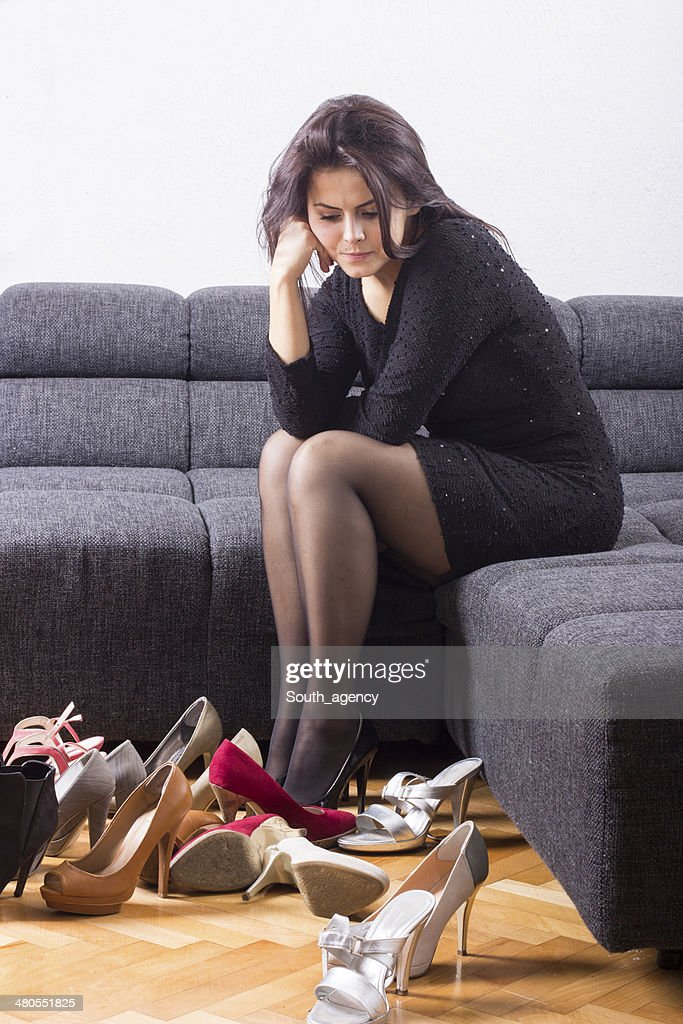 Beautiful girl chooses shoes in room : Stock Photo