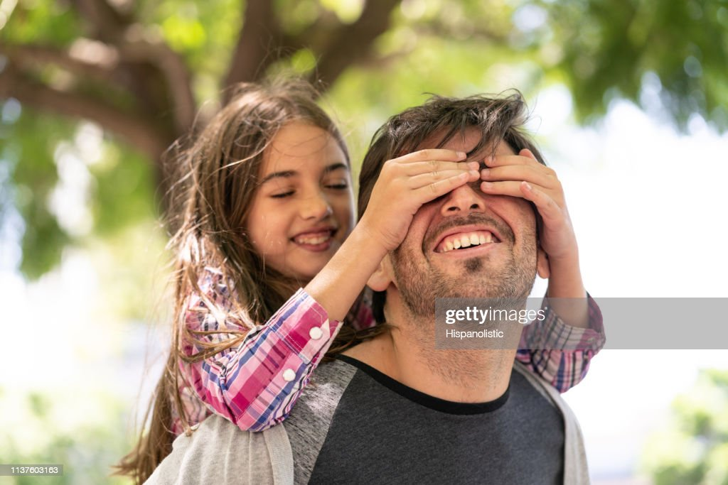 Beautiful girl covering her daddy's eyes while he carries her on back both smiling : Stock Photo
