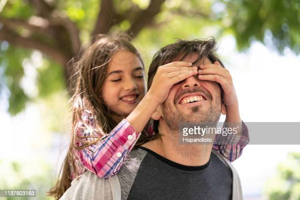 Beautiful girl covering her daddy's eyes while he carries her on back both smiling