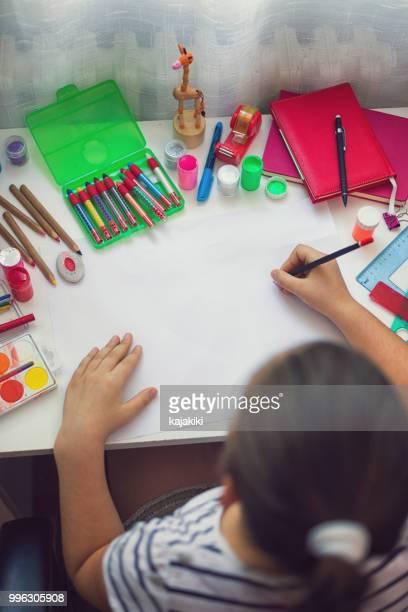 belle fille à faire leurs devoirs - écolière photos et images de collection