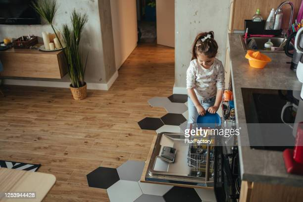 garota bonita fazendo tarefas domésticas sozinha - plastic plate - fotografias e filmes do acervo