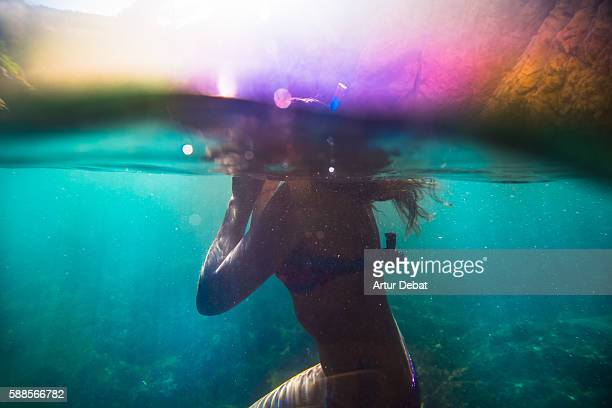 Beautiful girl doing snorkel with colorful bikini in the Mediterranean waters of Costa Brava on summer with underwater view in an idyllic place with vivid colors.