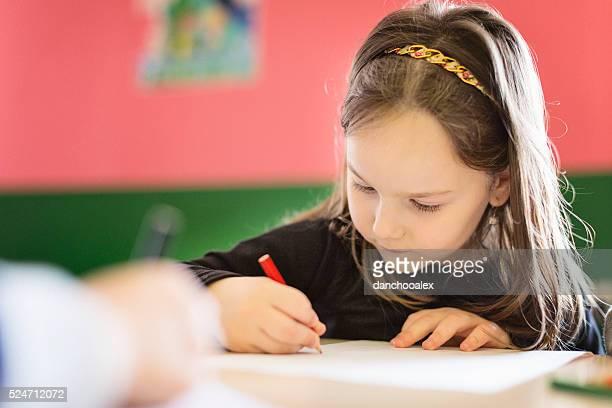 Beautiful girl drawing in the classroom