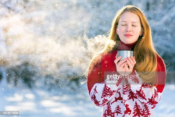 Schönes Mädchen trinkt heißes Getränk für winter