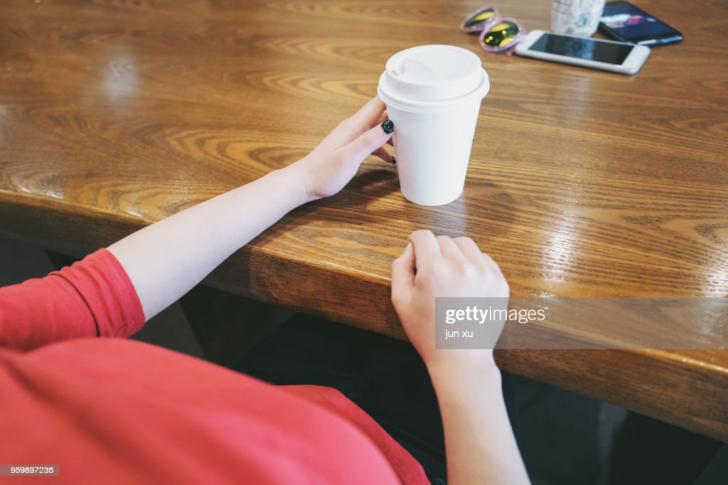 A beautiful girl drinks coffee at a coffee shop in kunming, yunnan province, China. : Stock Photo