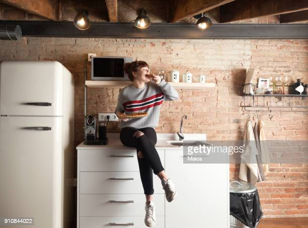 beautiful girl eating pizza in a modern kitchen - raparigas imagens e fotografias de stock