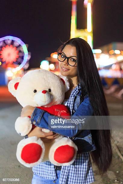 Beautiful girl embracing teddy bear in amusement park