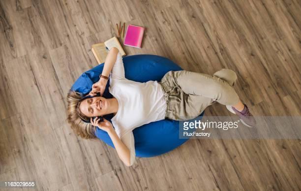belle fille appréciant la musique tout en prenant une pause de l'étude - sacco photos et images de collection