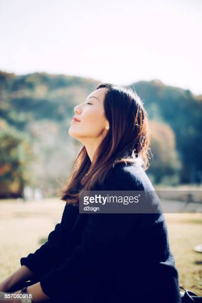 beautiful girl enjoying the fresh air under the sun - 頭をそらす ストックフォトと画像
