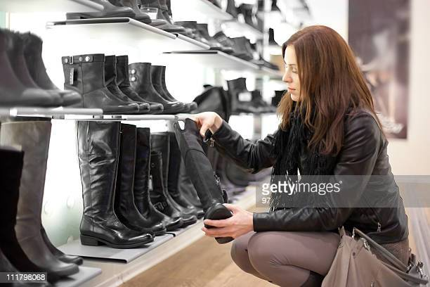 beautiful girl fits on a boots in  boutique.