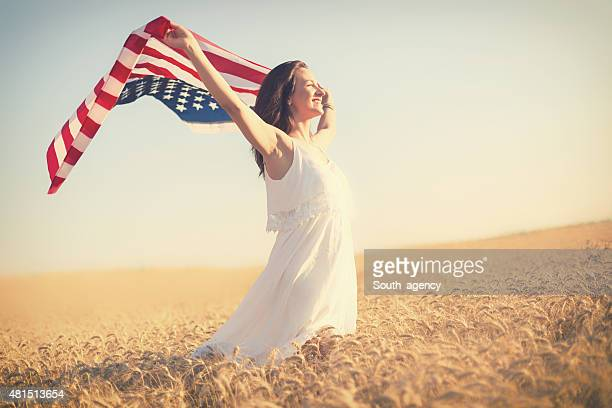 Beautiful girl holding an American flag in the wind