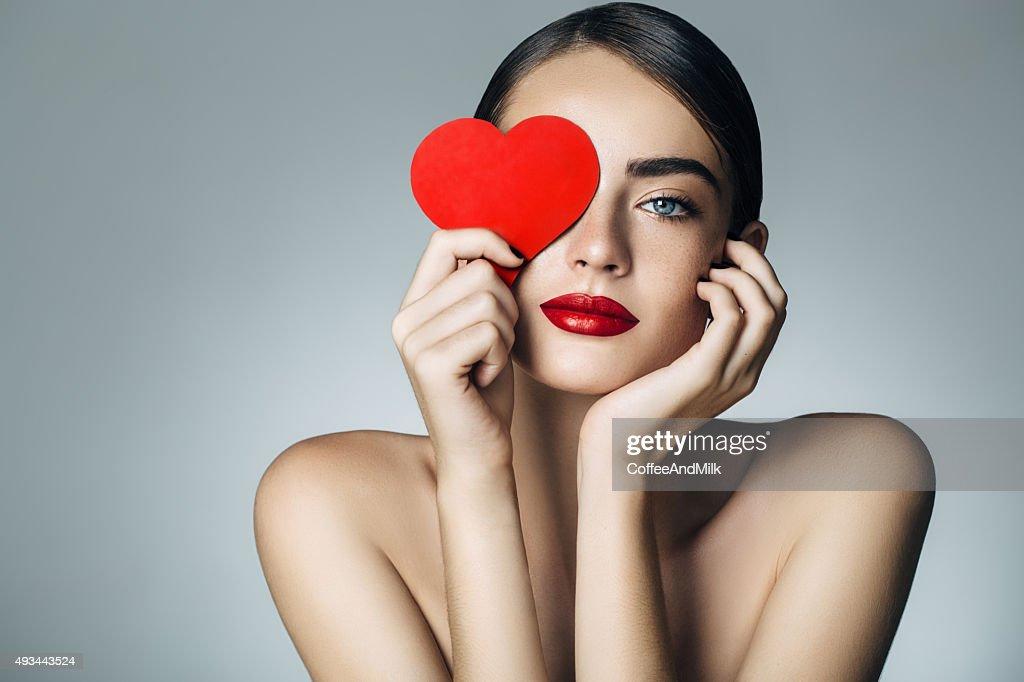 Beautiful girl holding artificial heart : Stock Photo