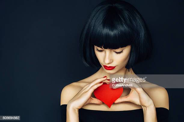 Beautiful girl holding artificial heart