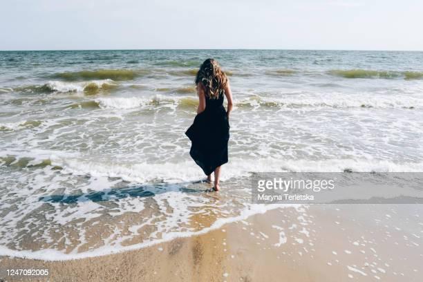 beautiful girl in a black dress runs along the beach. - schwarzes kleid stock-fotos und bilder