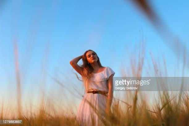 mooi meisje in een witte kleding op het gebied - witte jurk stockfoto's en -beelden