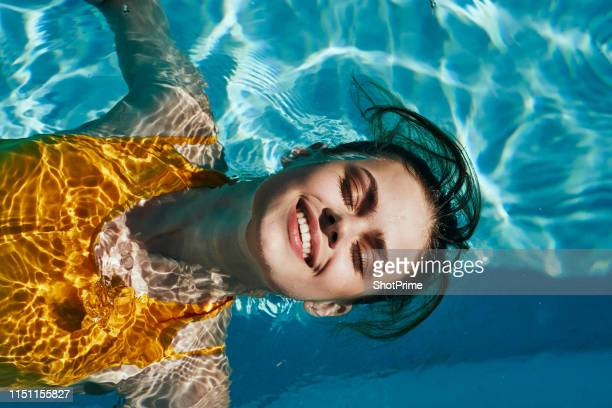 beautiful girl in a yellow swimsuit swims in the pool and smiling - blue hat stock pictures, royalty-free photos & images