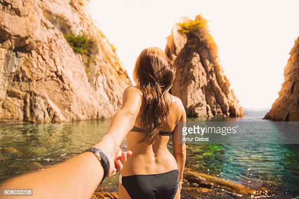 Beautiful girl in bikini lead the way in a stunning hidden beach between crags and beautiful island in the Mediterranean Sea Costa Brava on summer holding hands of his boyfriend showing him the place, taken from the guy personal perspective. Follow me.