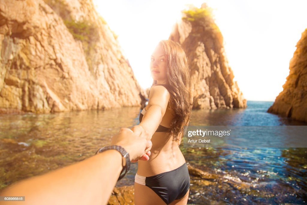 Beautiful girl in bikini lead the way in a stunning hidden beach between crags and beautiful island in the Mediterranean Sea Costa Brava on summer holding hands of his boyfriend showing him the place, taken from the guy personal perspective. Follow me. : Stock Photo