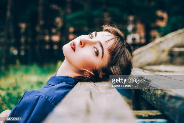 beautiful girl in blue shirt looks into camera - one young woman only stock pictures, royalty-free photos & images