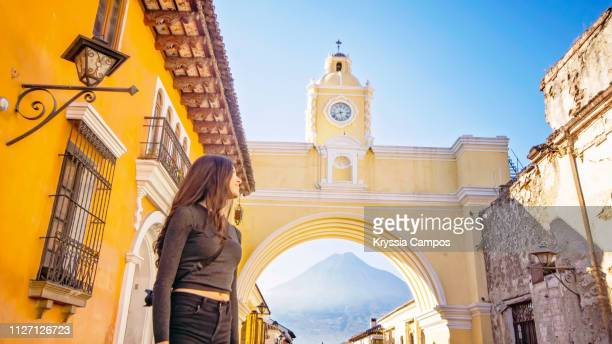 beautiful girl in front of arco de santa catalina (santa catalina arch) antigua guatemala - guatemala stock pictures, royalty-free photos & images