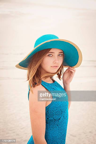 Beautiful girl in hat and blue dress on beach.