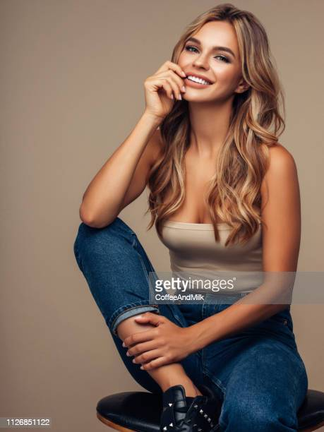 beautiful girl in jeans sits on the bar stool - blonde long legs stock pictures, royalty-free photos & images