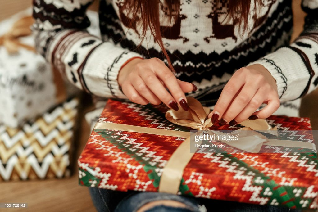 Beautiful girl in reindeer winter sweater unwrapping christmas present with golden ribbon, hands close-up, greeting card concept : Stock Photo