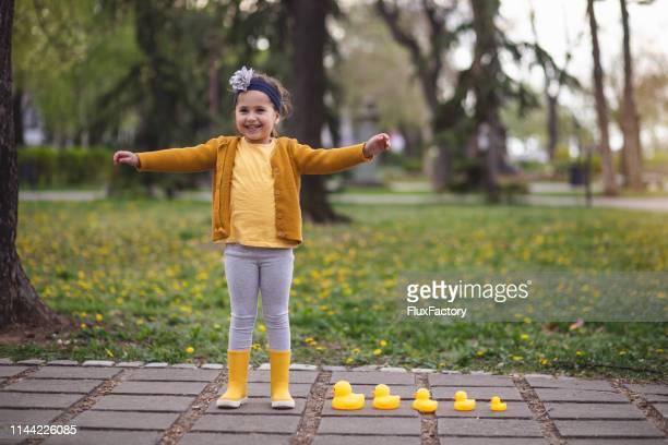 belle fille dans le parc public avec ses amis de canard de jouet - printemps humour photos et images de collection