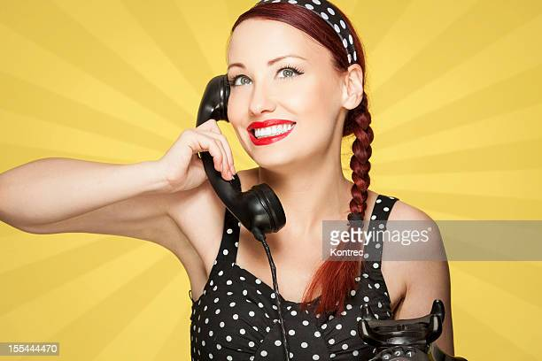 Beautiful girl in vintage dress talking on the telephone