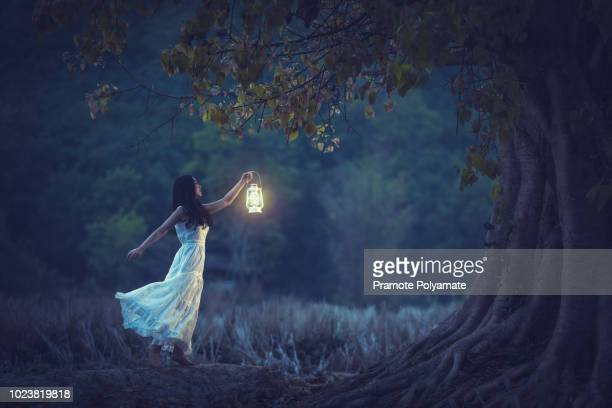 beautiful girl in white holding a lantern in the autumn forest shining under the trees. - ランタン ストックフォトと画像