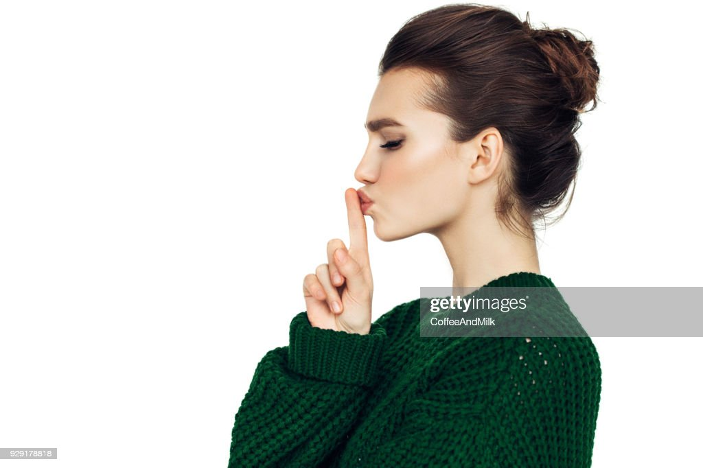 Beautiful girl indicates to be quieter : Stock Photo