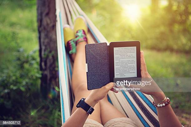 Beautiful girl is reading e-book in the hammock