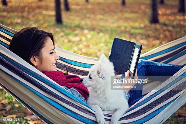 Beautiful girl is reading e-book in the hammock