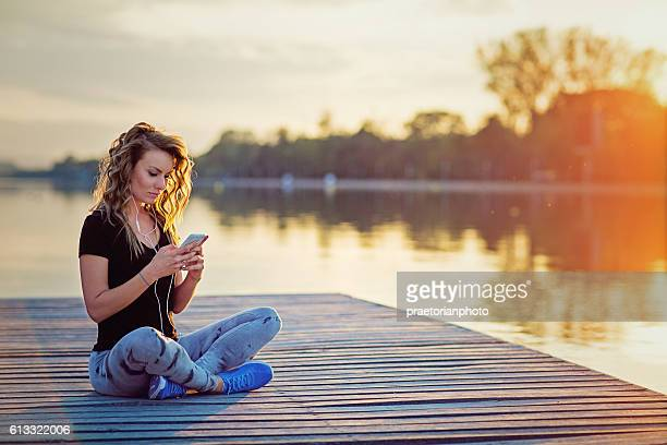 Beautiful girl is texting and listening the music