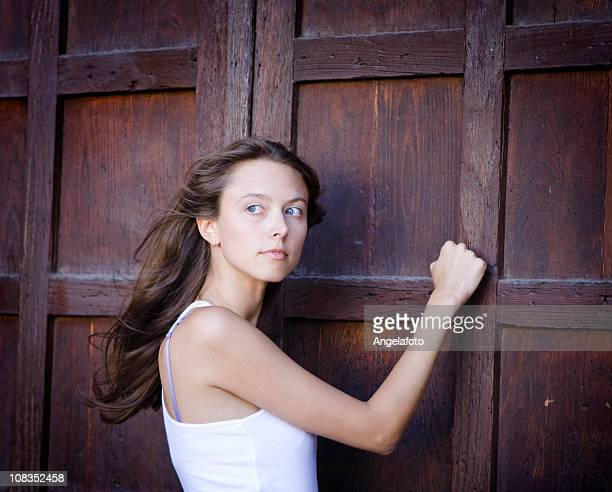 beautiful girl knocking on a door - knocking on door stock photos and pictures