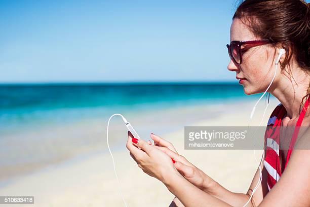 Belle femme écoutant de la musique sur la plage