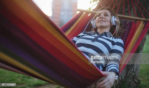 Vacker flicka liggande i en hängmatta och dag drömmer
