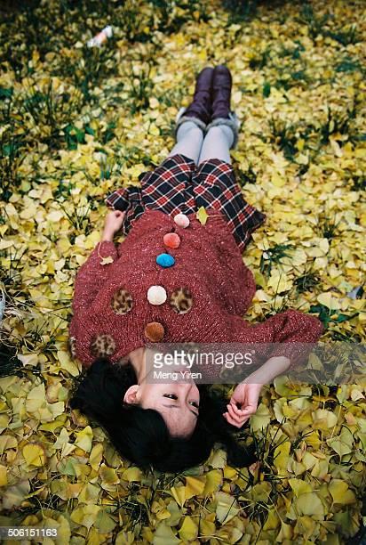 Beautiful girl lying on the gingko leaves ground